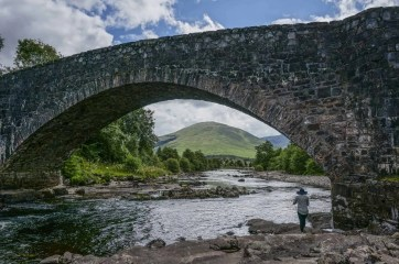 Bridge of Orchy frames the green hills beyond.
