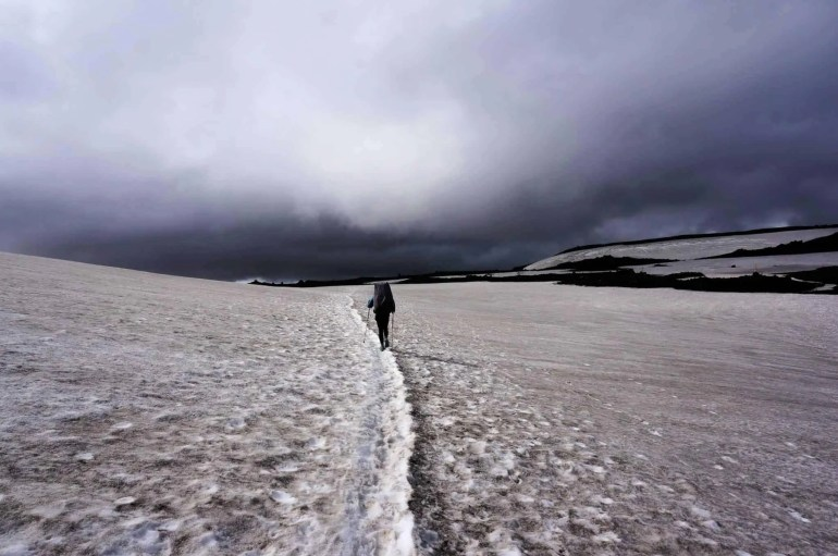 A hiker walks through a large snow field on the Laugavegur Trail