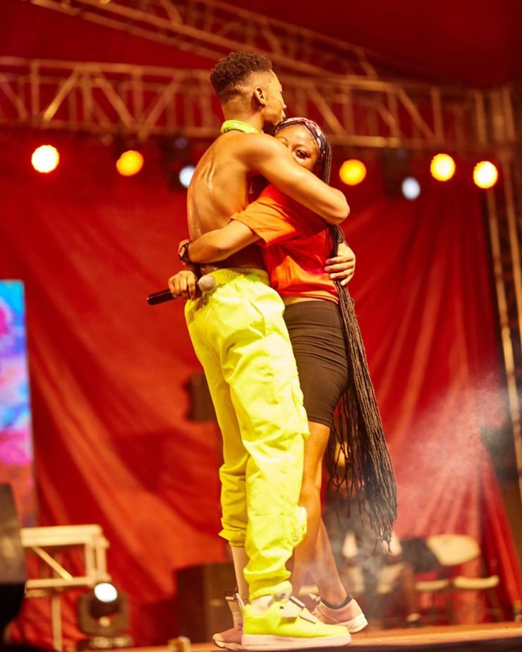 Kidi hugs a fan who joined him on stage to perform.