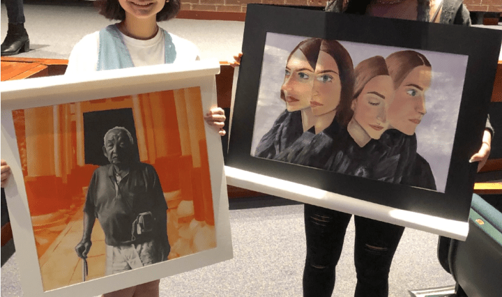 Photo of TMI Students Sara Homma and Kristina Samuel displaying their artwork at the Feb. 23 regional Visual Arts Scholastic Event at John Paul Stevens High School.