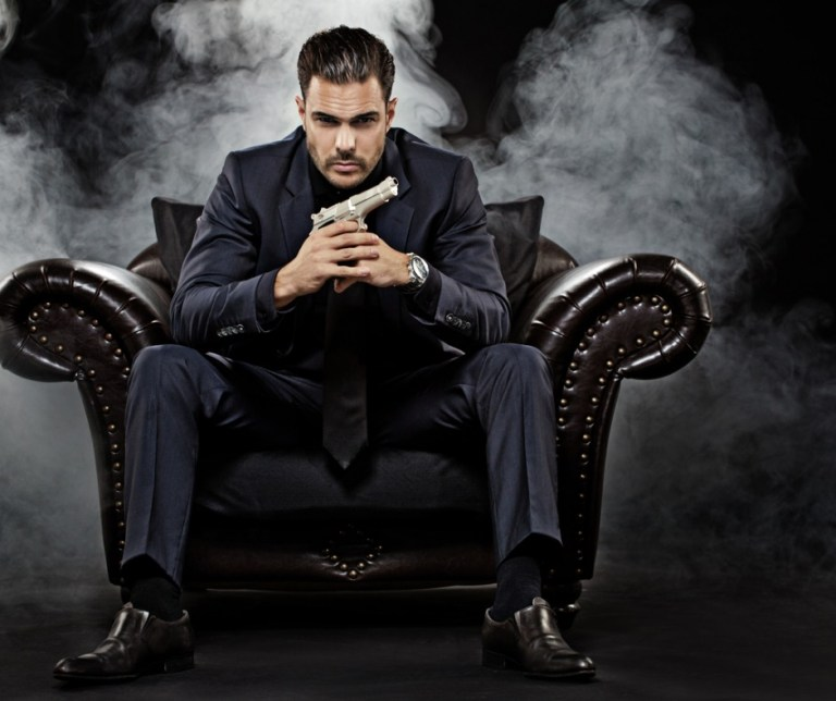 gangster-holding-gun-sitting-on-chair-picture-id471985004