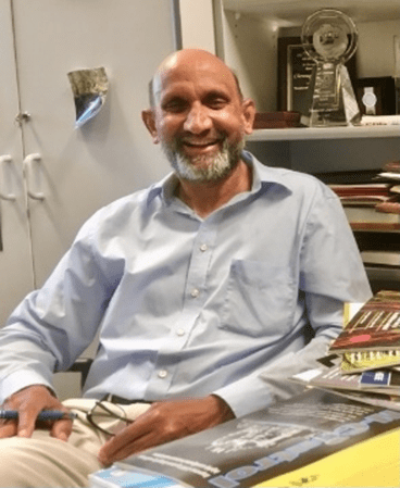 Professor Jagadish is smiling while seated at his desk