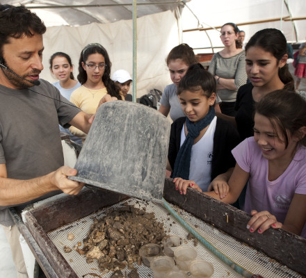 Zachi sifting with young volunteers