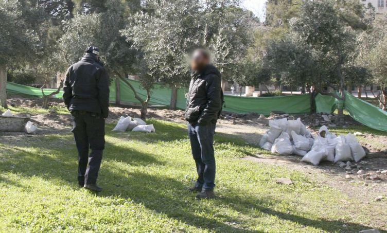 שוטר וארכיאולוג מרשות העתיקות מפקחים על עבודות החפירה