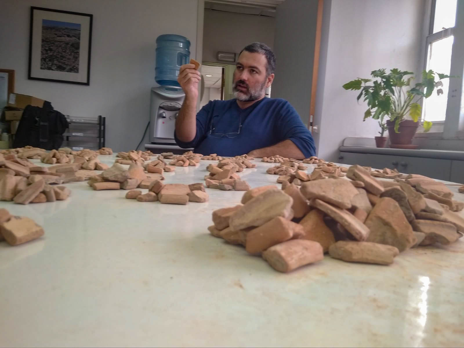 Researcher inspecting a pottery shard in front of a table containing heaps of pottery shards.