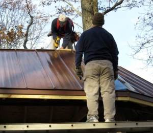 Painter & Gilson work on metal roof cap.
