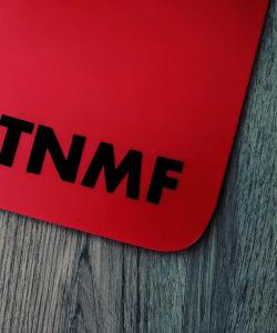 T N M F black sticker on a red mudflap