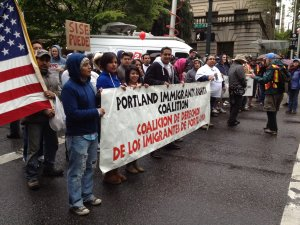 At the front of a May Day protest march, people holding Portland Immigration Coalition banner.