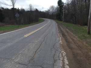A picture of a two-lane country road going up a hill.