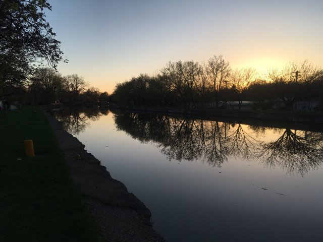 A an evening view of the Erie Canal. The water is smooth as glass, and the trees, still bare late in the spring, reflect off of it.