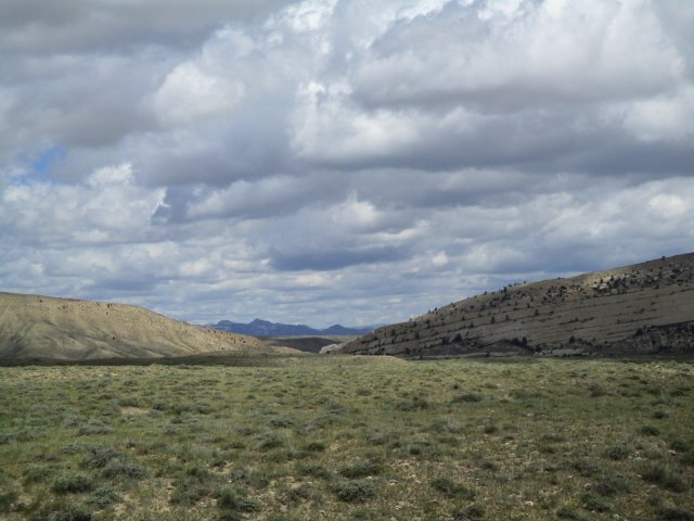 A prairie in the foreground with two hills in the middle distance and mountains in the far distance.