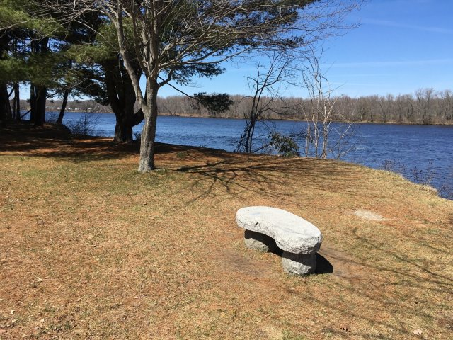 A small stone bench along Brunswick bike pathe with the Androscoggins River and a blue sky in the background.
