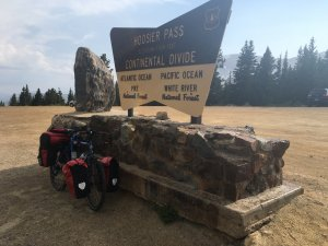 A loaded tour bike at the sign marking the Continental Divide at Hoosier Pass, elevation 11,529 ft