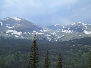 Rocky Mountain peaks with snowfields. The sky is grey with the threat of rain.