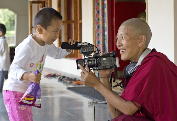 Tibetan Buddhist nun with video camera filming child