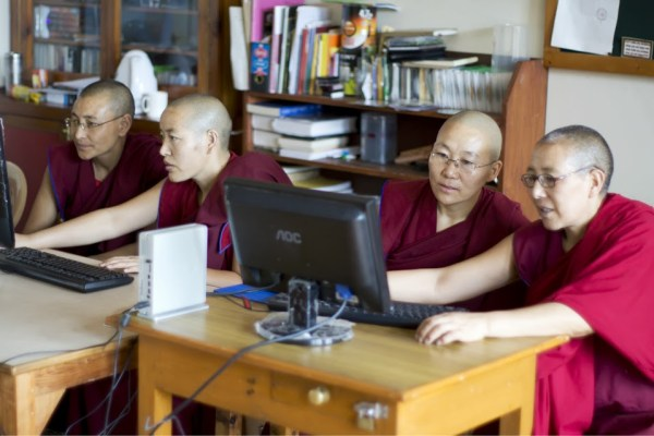 picture of 4 Tibetan Buddhist nuns at computers