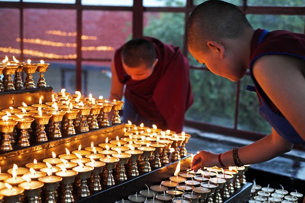 Tibetan Buddhist nuns at Dolma Ling Nunnery lighting butter lamps. Photo courtesy of Brian Harris