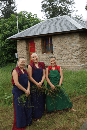 3 Tibetan Buddhist nuns in front of retreat huts