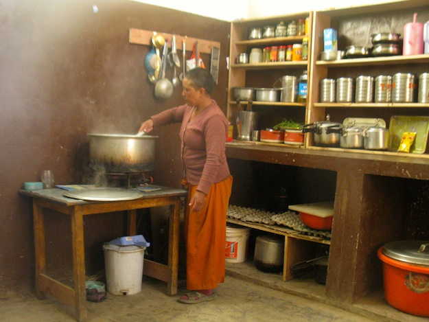 Tibetan Buddhist nun working in kitchen