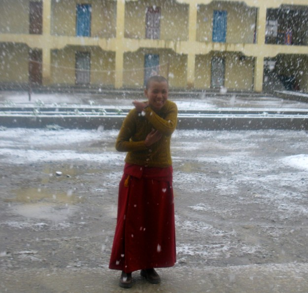 Tibetan Buddhist nun in snowfall at Sherab Choeling Nunnery