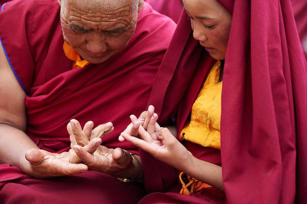 Senior nun shows young nun a hand mudra