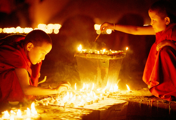 young monastics light butter lamps at Mahabodhi Temple Bodhgaya