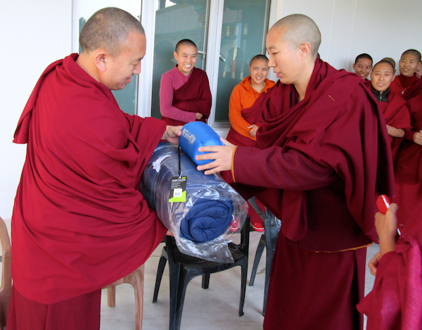 Tibetan Buddhist nun receiving gift of sleeping bag