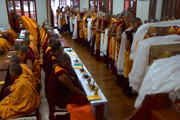 Nuns offering prayer scarves to portrait of His Holiness the Dalai Lama