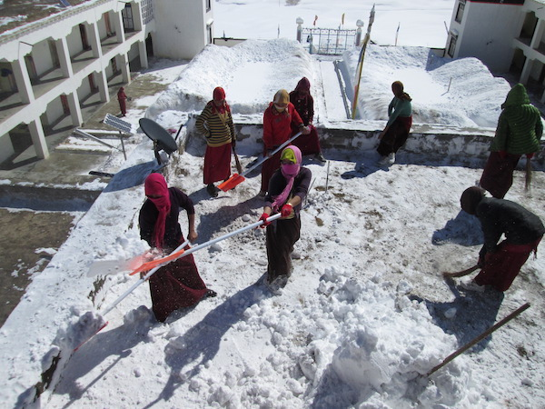 Tibetan Buddhist nuns shovel snow from the nunnery roof
