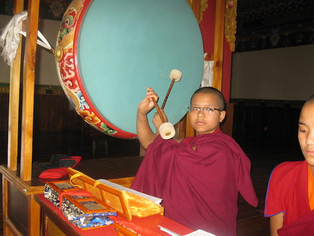 young Tibetan Buddhist nun performs a puja at Tilokpur