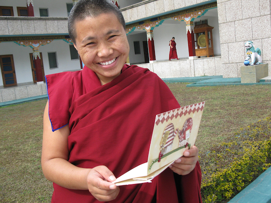 Tibetan Buddhist Nun at Sakya College for Nuns holding card from her sponsor