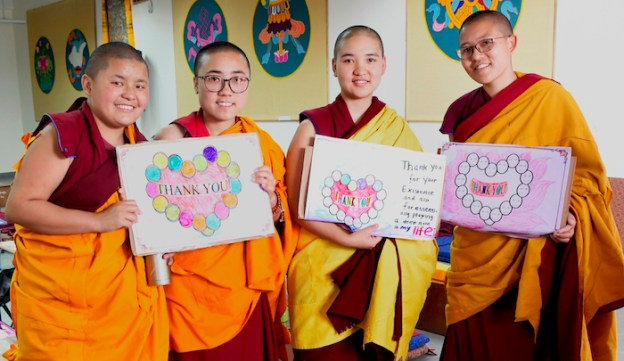 Tibetan Buddhist nuns hold thank you signs