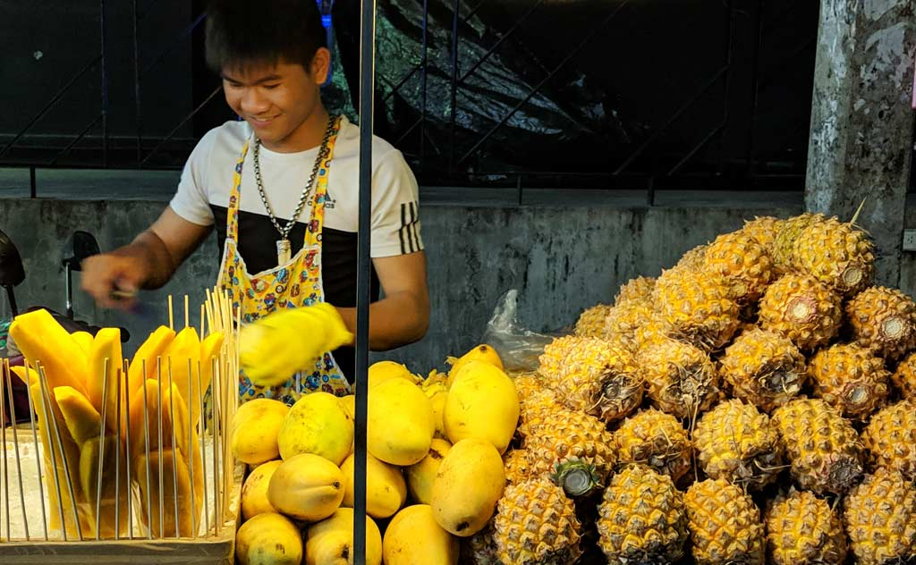 A Thai Vendor selling pineapples and mangoes