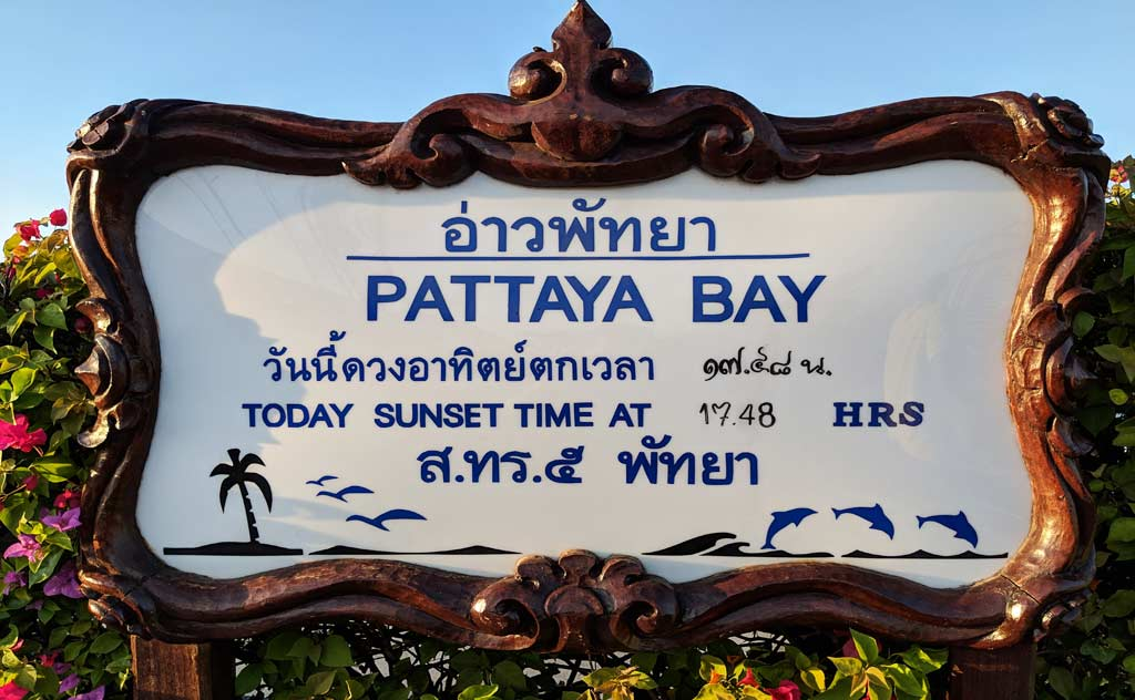 Board showing sunset time at Pattaya bay