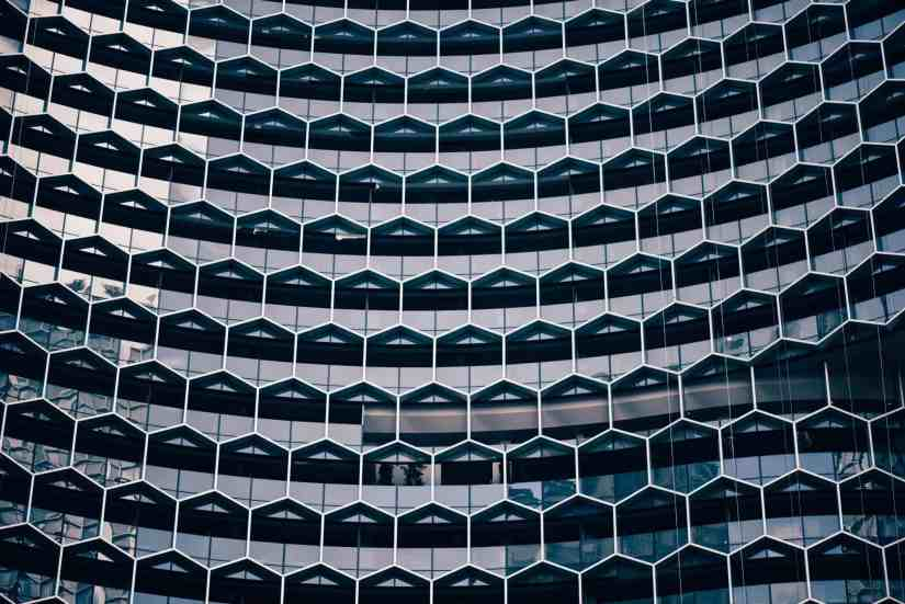"""Selbstorganisation: """"A honeycomb pattern in the facade of a modern office building"""" by chuttersnap on Unsplash"""