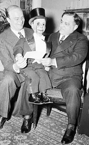 """20 Mar 1939, Manhattan, New York, New York, USA --- New York: Blockhead Calls On The Mayor. That brainless wonder, that inimitable blockhead, Charlie McCarthy, is shown as he called at New York's City Hall to present Mayor Fiorrello La Guardia with his invitation to the forthcoming Press Photographer's Ball. Charlie sits on the Mayor's knee as Edgar Bergen, left, the dummy's """"voice,"""" puts words in his mouth. Actress Dorothy Lamour gets a kick out of the proceedings. --- Image by © Bettmann/CORBIS"""