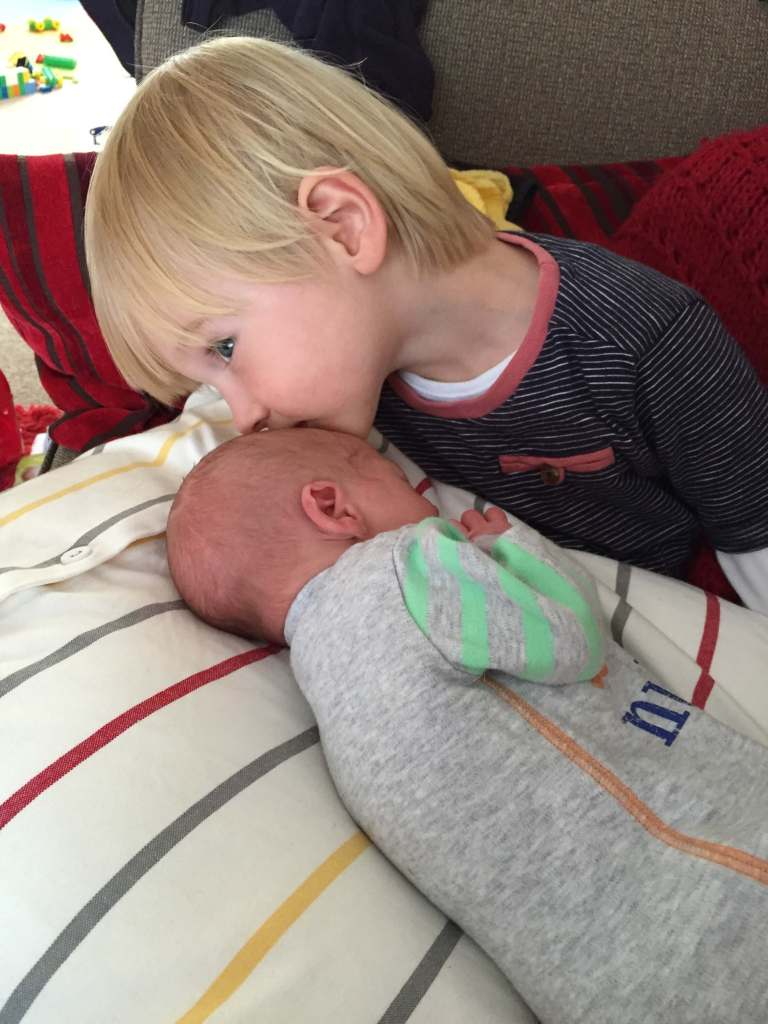 Toby giving newborn Gabe a kiss on the head