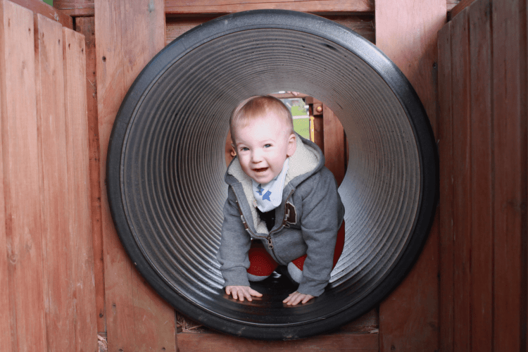 Gabe exploring the tunnel in the play area at Bluestone