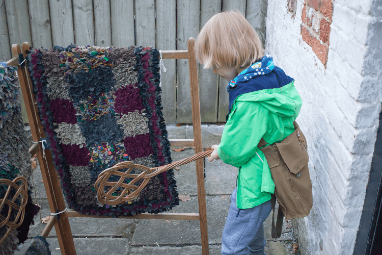 Toby beating a rug at Quarry Bank Mill