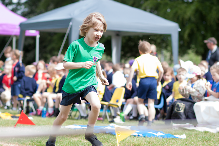 Toby racing for the finish line in the obstacle race at school sports day