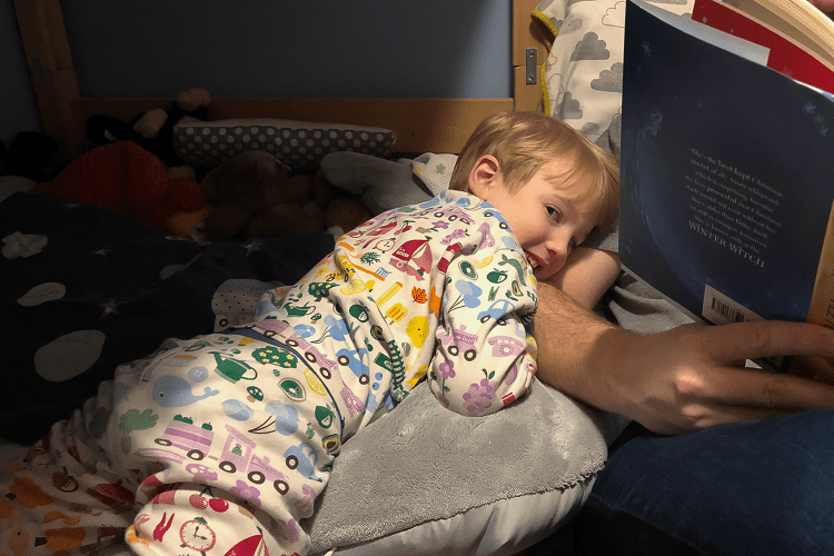 A small boy cuddling up to a man's arm which is holding a book