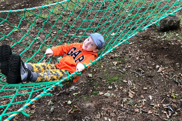 Gabe swinging in a hammock in the woods