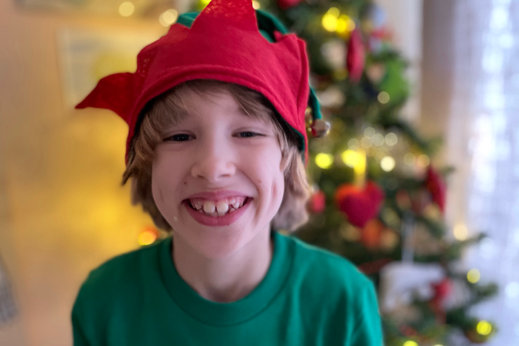 Toby wearing an elf hat in front of the Christmas tree