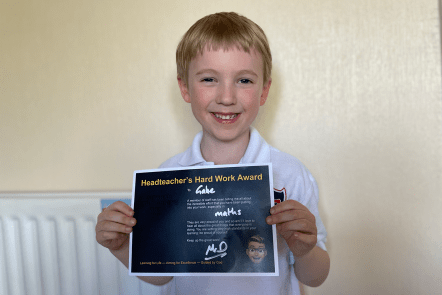 Gabe with a certificate from school