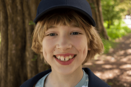 Close up of Toby smiling and wearing a cap