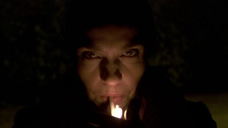 La cara de una persona encendiéndose un cigarrillo en la oscuridad. Solo está iluminada por la llama del mechero.