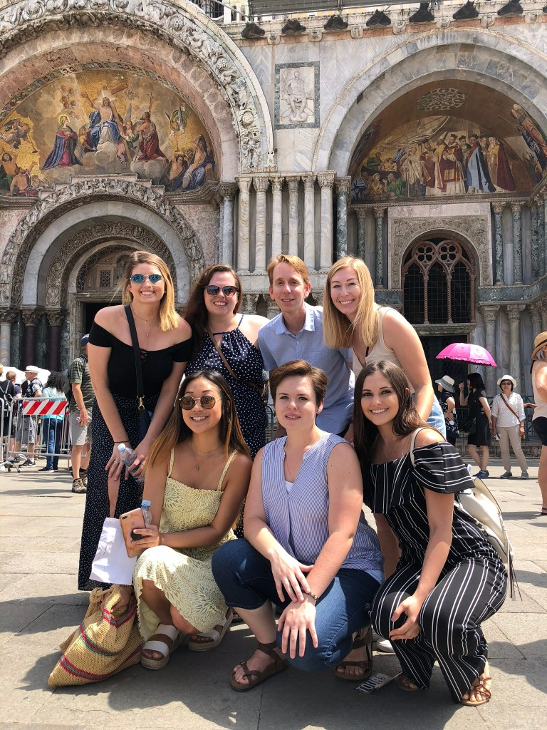 A professor and his students pose in a busy public square in Verona, Italy.