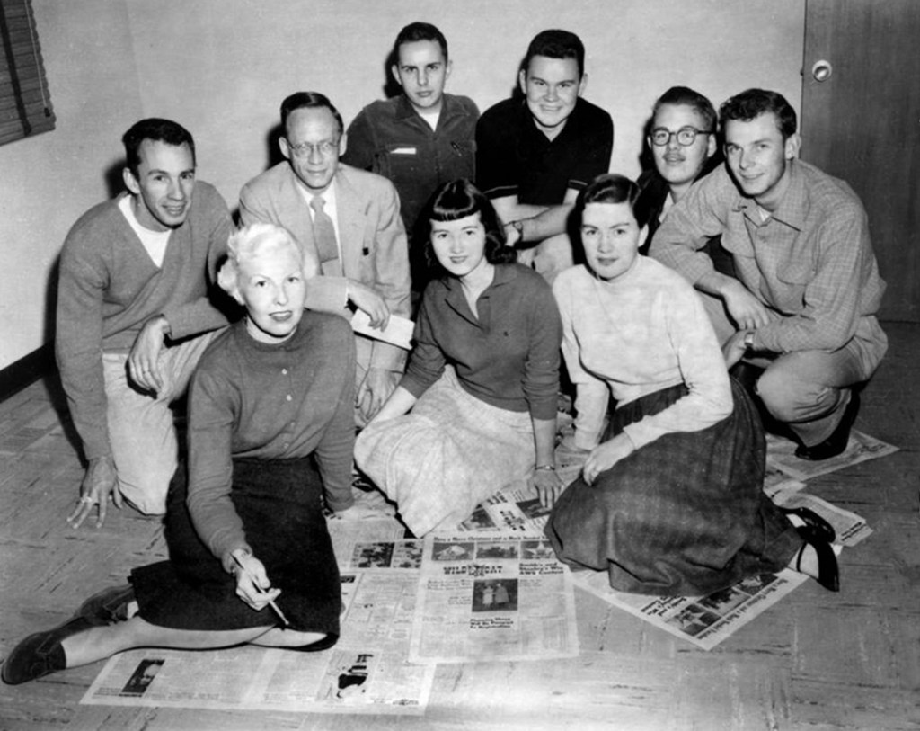 Black and white photo of Faye kneeling on a collection of Wildcat newspapers surrounded by a team of students in collared shirts or long skirts customary to the time.