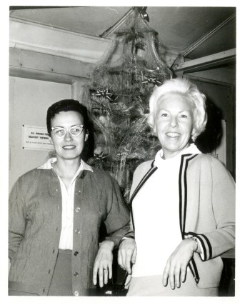 Black and white photo of Faye and another woman standing in front of a Christmas tree.