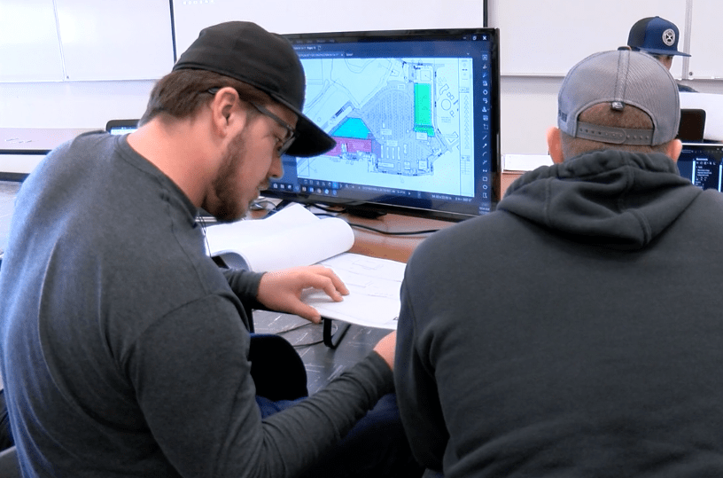 Two students work on complicated engineering problems.